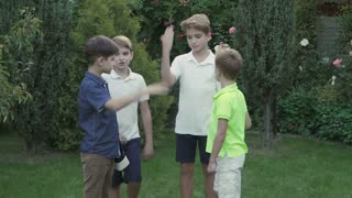 Team of four brothers puts hands one on another in the garden