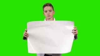 Teenager holds an empty paper at green background