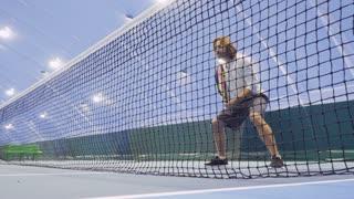 Tense man with tennis racquet wait the tennis ball to hit it