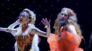 The actors in crazy costumes are singing and dancing on the stage in theatre