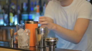 The barman shakes the cocktail in an orange shaker on a bar
