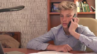 The boy is talking by phone in bedroom