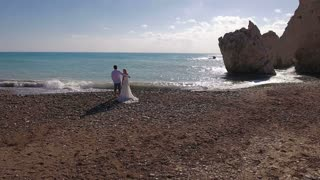 The bride and groom stand in embrace on the beach