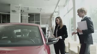 The businesswoman inspects a car's cabin in car showroom