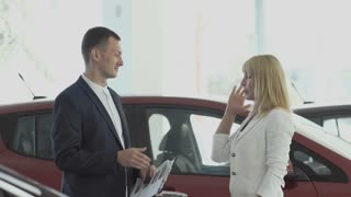 The car seller and elegant businesswoman makes a deal about buying car