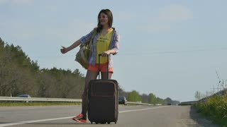 The car stops near the girl hitchhiker