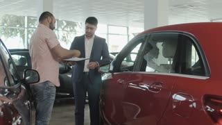 The couple buys a new car in car dealership
