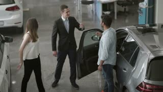 The couple of young people buys a car in car showroom