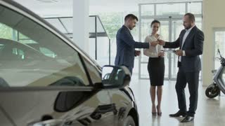 The couple signs the contract of buying car in the car showroom and gets key