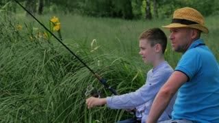 The dad teaching his son a fishing