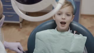 The dentist checks the teeth of little boy with angular probe and mirror