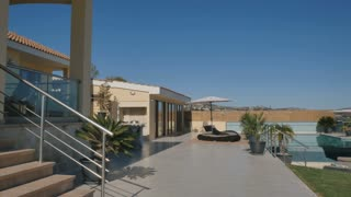 The exterior of modern villa with terrace, swimming pool and deck chair