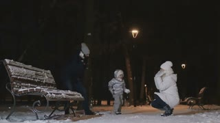 The father and little daughter throws the snow into a young woman in slowmotion