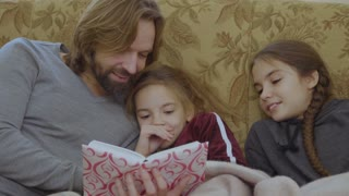 The father reads fairytale to daughters