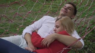 The guy hugs a girl in a hammock
