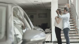 The guy makes a gift automobile to girlfriend in car dealership
