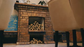 The interior of a cafe with a fireplace and firewood