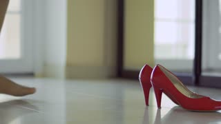 The legs of the girl wear red shoes