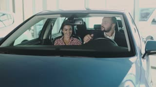 The man and woman sits in the modern car in car dealership and talking