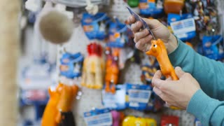 The man choose the toy for his dog in pet-shop