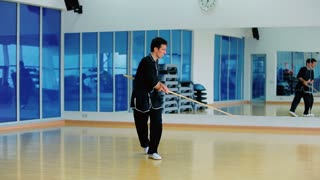 The man in black costume fighting with stick with invisible opponent in the gym