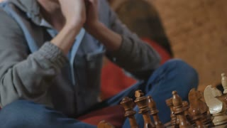 The man made a move as a bishop during playing chess