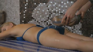 The man pours the water on a girl's body in Turkish bath