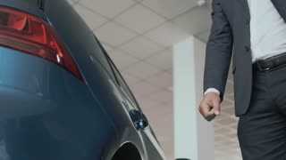 The man puts the charging into a power socket of modern electric car