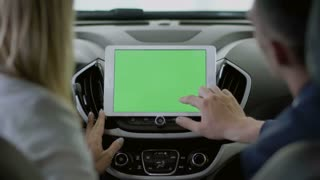 The manager shows the information on tablet to the woman inside the car