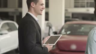 The manager with tablet shows the cars to customer in car showroom