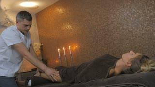 The masseur massaging the girl's legs in the massage salon