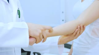 The medical expert explore the girl's elbow in clinic