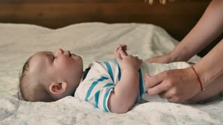 The mother changes the diaper of the baby on the bed