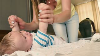 The mother makes a sports exercises with lying baby on the bed