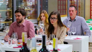 The people tasting a white wine on the degustation