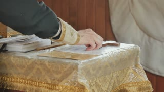 The priest corrects the cross on the table and crosses himself