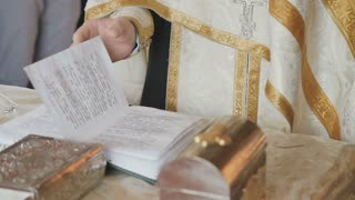 The priest is reciting a prayer and crosses himself during the ritual