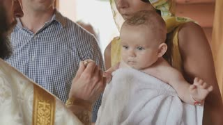The priest makes a ritual of anointing with oil during the infant baptism