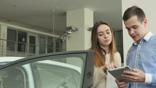 The salesman and woman talks about car in car dealership