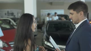 The salesman discuss the deal of buying a car with woman in car dealership