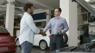 The salesman give the keys to a buyer in car showroom