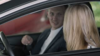 The salesman gives a car keys to happy businesswoman in car dealership