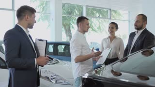 The salesman greets the couple with car purchase in the car showroom