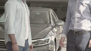 The salesman shakes hands with buyer after buying the car