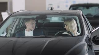The salesman talks about car characteristics to stylish businesswoman inside car