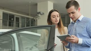 The salesman with tablet and young businesswoman in car dealership