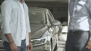 The seller give a keys and shake hands with customer in car showroom