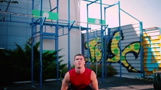 The sportsman training with barbell outdoor