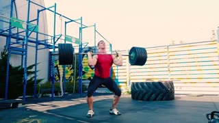 The sportsman training with heavy barbell on the sports ground