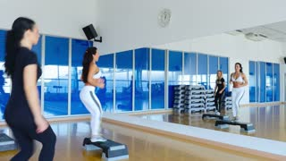 The sporty women training step aerobics in gym with step